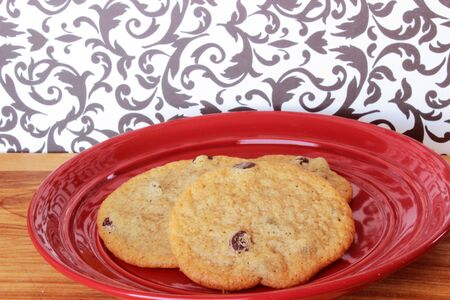 A close-up image of three delicious home made chocolate chip cookies on a red plate, on a wooden counter with a retro black and white wallpaper background