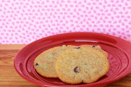 A close-up image of three delicious home made chocolate chip cookies on a red plate, on a wooden counter with retro pink paisley wallpaper. Stock Photo