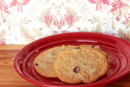 A close-up image of three delicious home made chocolate chip cookies on a red plate, on a wooden counter with elegant red and white flowered vintage wallpaper.