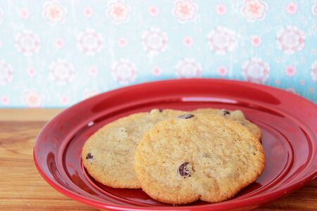 A close-up image of three delicious home made chocolate chip cookies on a red plate, on a wooden counter with vintage pink and blue flowered wallpaper. Stock Photo