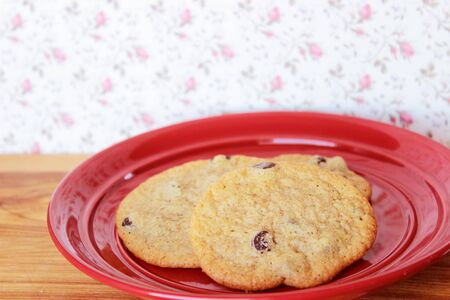 A close-up image of three delicious home made chocolate chip cookies on a red plate, on a wooden counter with vintage pink and white rosebud wallpaper.