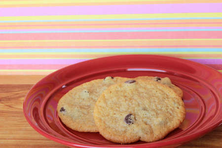 A close-up image of three delicious home made chocolate chip cookies on a red plate, on a wooden counter with colorful pink, yellow, and orange striped  wallpaper. Stock Photo
