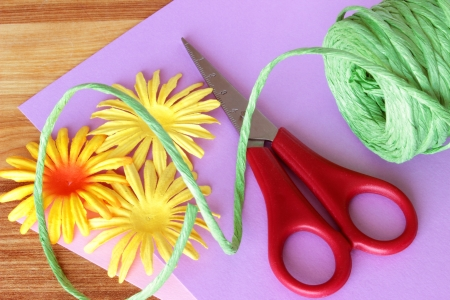 A close up image of colorful craft supplies, including scissors, raffia ribbon, paper flowers, and craft paper, on a wooden table.