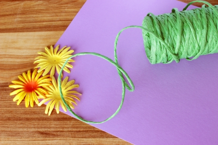 A close up image of colorful craft supplies, including raffia ribbon, paper flowers, and craft paper, on a wooden table.