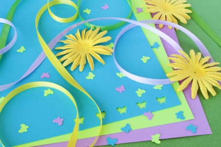 A spring themed collection of card making or scrapbooking supplies, including yellow paper flowers, colorful ribbons, and butterfly shaped confetti.