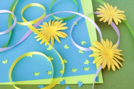 A spring themed collection of card making or scrapbooking supplies, including yellow paper flowers, colorful ribbons, and butterfly shaped confetti. Reklamní fotografie - 17443916