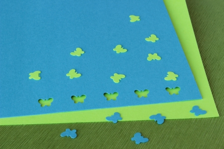 An image of card making or scrapbooking supplies: green and blue butterfly confetti and a punched sheet of cardstock.