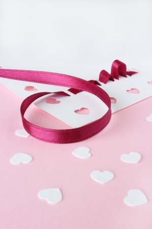 A close up image of card making supplies, including red ribbon and white heart confetti, on a pink background.