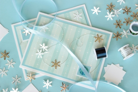 brads: An image of two hand made greeting cards with a winter theme, with card making supplies including snowflake shaped brads and craft wire.