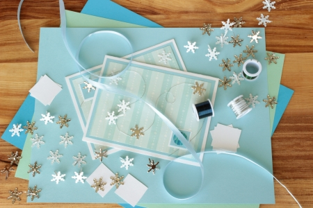 An image of two hand made greeting cards with a winter theme, with card making supplies including snowflake shaped brads and craft wire.