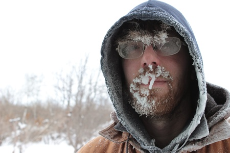 A close up image of a man with frosted glasses and facial hair on a cold, overcast winter day  Stock Photo