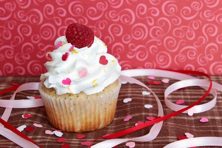 A lemon poppyseed cupcake with a swirl of buttercream icing and a raspberry on top, on a brown plaid tablecloth with heart shaped confetti and sprinkles, and pink and red ribbons, with a red background with pink swirls