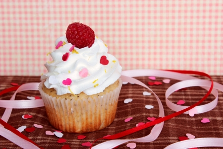 A lemon poppyseed cupcake with a swirl of buttercream icing and a raspberry on top, on a brown plaid tablecloth with heart shaped confetti and sprinkles, and pink and red ribbons, with a pink gingham background