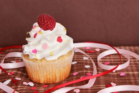 A lemon poppyseed cupcake with a swirl of buttercream icing and a raspberry on top, on a brown plaid tablecloth with heart shaped confetti and sprinkles, and pink and red ribbons, with a brown background