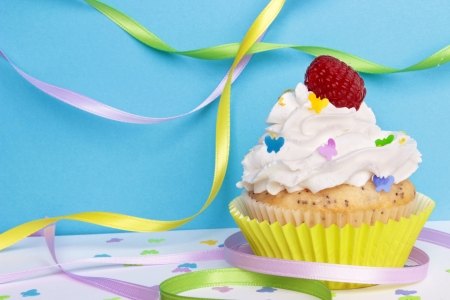 A lemon poppyseed cupcake with a swirl of buttercream icing, lemon zest, and a raspberry on top, on a blue background with butterfly confetti and sprinkles, and colorful ribbons    Stock Photo