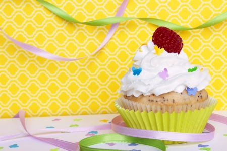 A lemon poppyseed cupcake with a swirl of buttercream icing, lemon zest, and a raspberry on top, on a yellow patterned background with butterfly confetti and sprinkles, and colorful ribbons    Stock Photo