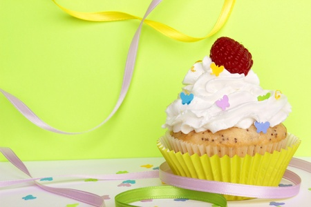 A lemon poppyseed cupcake with a swirl of buttercream icing, lemon zest, and a raspberry on top, on a green background with butterfly confetti and sprinkles, and colorful ribbons    Stock Photo