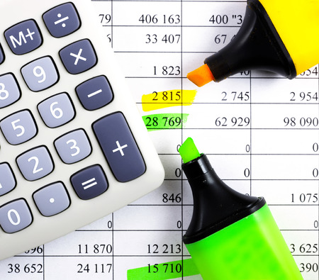 Calculator, highlighter and markers on financial statements.