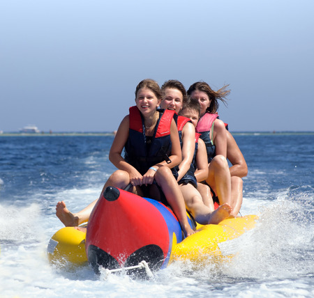 happy people having fun on banana boat on the red sea