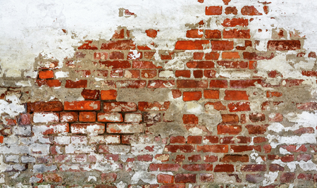 Vintage red brick wall with peeled plaster. Grunge red stonewall background. Shabby building facade with damaged plaster.