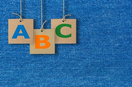school of fish: ABC letters on cardboard label with rope on jeans texture background. Alphabet logo.