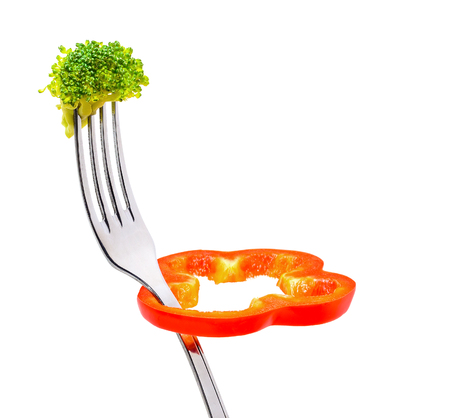 dietetics: Concept diet and weight loss. Fresh broccoli, slice of red pepper rotates on a fork. Isolated on white.