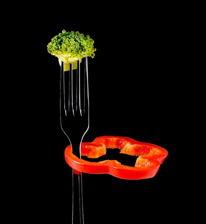 dietetics: Concept diet and weight loss. Fresh broccoli, slice of red pepper rotates on a fork. Isolated on black background