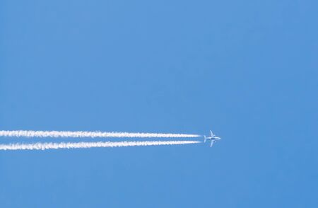 Horizontal trace of plane flying in blue sky Stock Photo