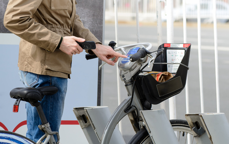 Man taking a bicycle in a bike sharing city service