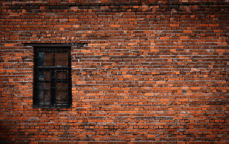 Old black brick wall and window locked with metal bars