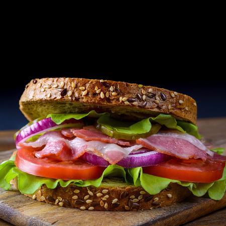 freshly prepared: Freshly prepared sandwich with bacon, tomato, cucumber, onion on whole grain wheat toast on dark background. Stock Photo