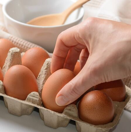 Woman taking raw egg from packaging
