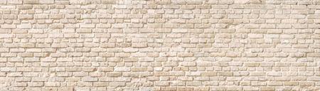 Beige old brick wall panorama.