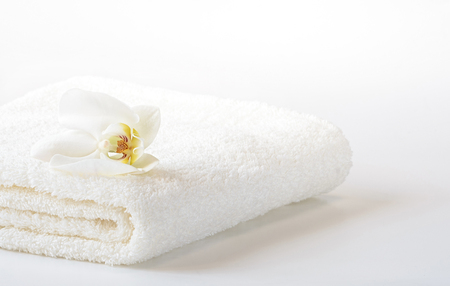 White Spa towel with Orchid flower on white background