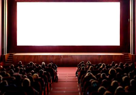 Ludzie w sali kinowej z pustym białym ekranem. Zdjęcie Seryjne