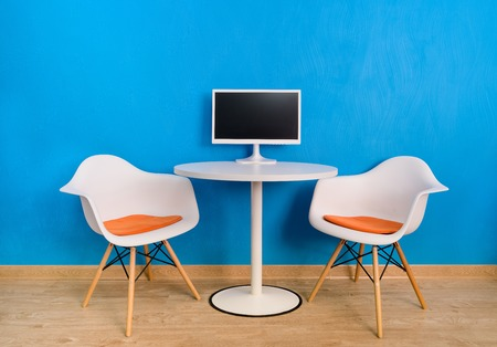 Modern interior office table and two chairs with computer monitor