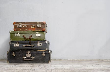 Old suitcases stack near the white wall