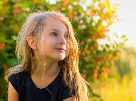 Portrait of little blond girl at sunset