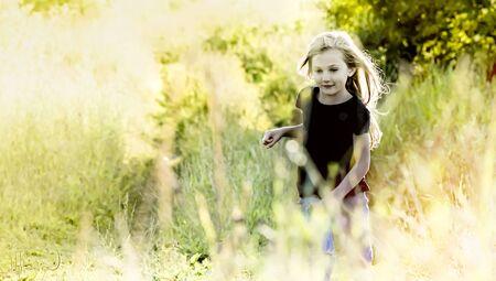 Little blond girl running at sunset