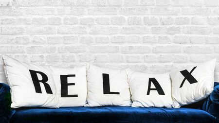 Blue sofa and white pillows with letters RELAX on brick wall background.