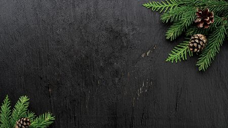 Christmas Fir tree branches and pine cones on a black wooden board Imagens - 127616845