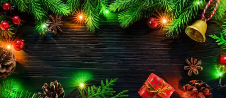 Christmas banner. Fir tree garland with glowing christmas tree decorations on black wooden board.