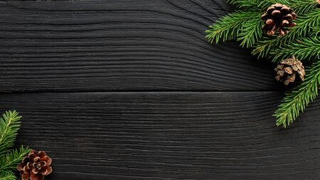 Christmas Fir tree branches and pine cones on a black wooden background. Banco de Imagens