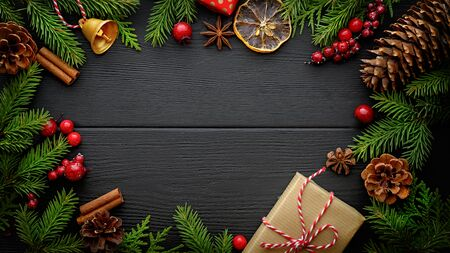Fir tree branches and christmas decorations on black wooden background with copy space