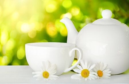 White cup of tea and teapot with chamomile flowers on white wooden table.