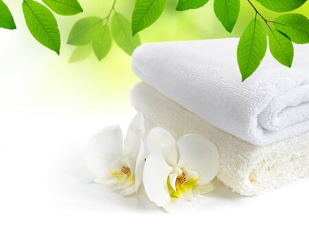 Spa towels with white Orchid flowers and green leaves on white