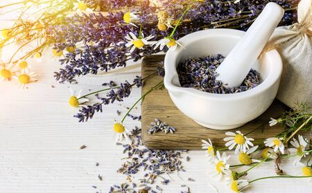 White mortar with Dry lavender and camomile flowers on white wooden background. Banco de Imagens - 128592226