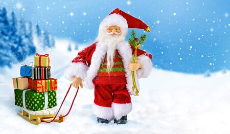 Santa Claus with gift boxes on snowy landscape background . 版權商用圖片