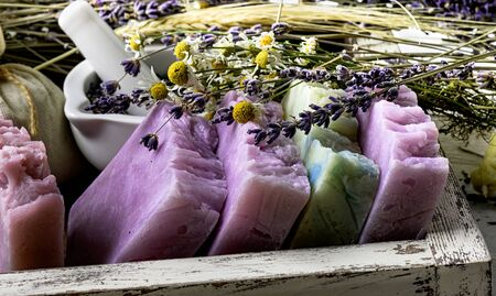 Handmade Soap with dried lavender and chamomile flowers with white ceramic mortar in wooden box. Stock Photo