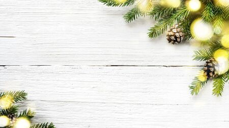 Christmas tree branches and pine cones on white wooden background.